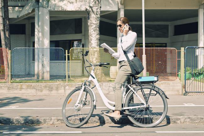 E-bike banlieue s'arrêter dans la rue et appeler avec un téléphone mobile . — Photo de stock