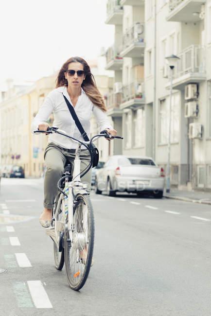 Büroangestellte mit E-Bike auf dem Weg zur Arbeit in der Stadt. — Stockfoto