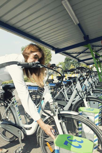 Пригородные женщины берут электронный велосипед со станции обмена велосипедами . — стоковое фото