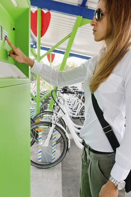 Female commuter taking electric bicycle from bicycle sharing station. — Stock Photo