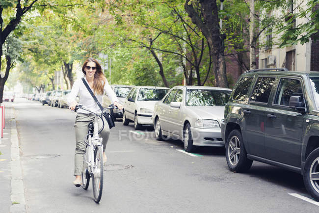 Woman riding electric bicycle on city street. — Stock Photo