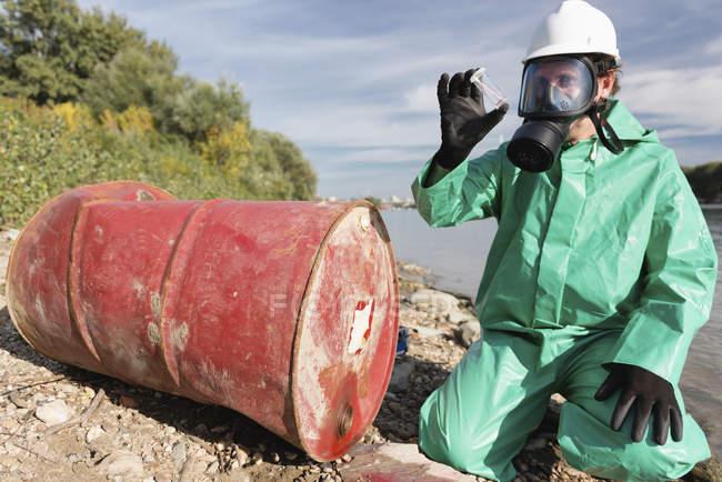 Inspecteur de contrôle de la pollution regardant l'échantillon de produit chimique fuite à côté de la rivière. — Photo de stock