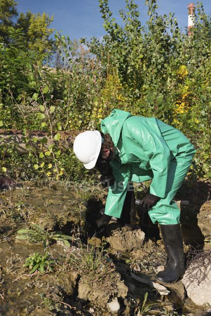 Inspecteur de contrôle de la pollution prenant l'échantillon de l'eau polluée du ressort dans le domaine. — Photo de stock