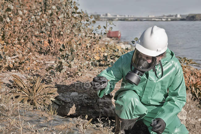 Pollution control inspector taking sample of mud in field by lake. — Stock Photo