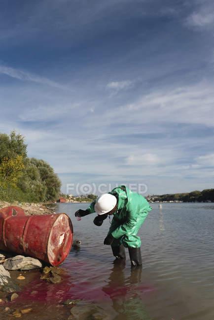 Inspecteur de contrôle de pollution dans la combinaison protectrice prenant l'échantillon de la substance toxique s'échappant du tambour d'huile. — Photo de stock