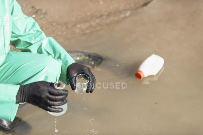 Environment worker taking sample of polluted water at pollution site. — Stock Photo