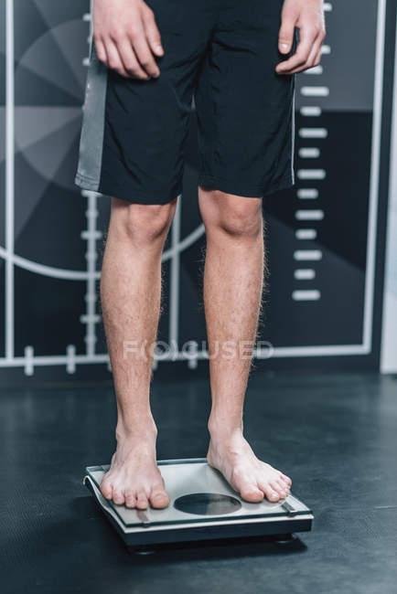 Sezione bassa dell'adolescente in piedi sulle bilance di pesatura. — Foto stock