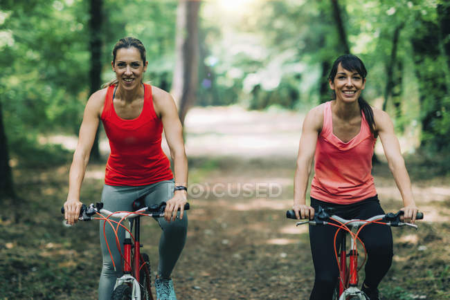 Cheerful female friends riding bikes together in park. — Stock Photo