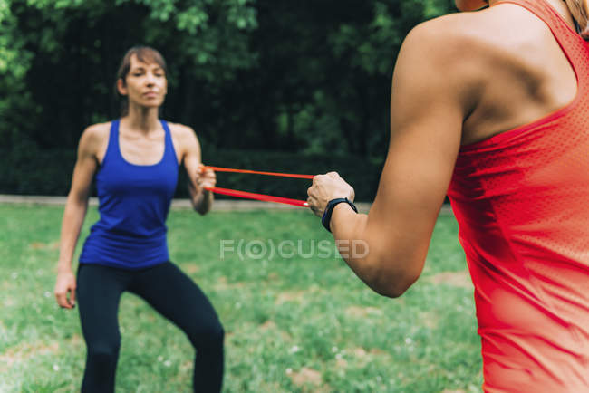 Female friends exercising with elastic band in park. — Stock Photo