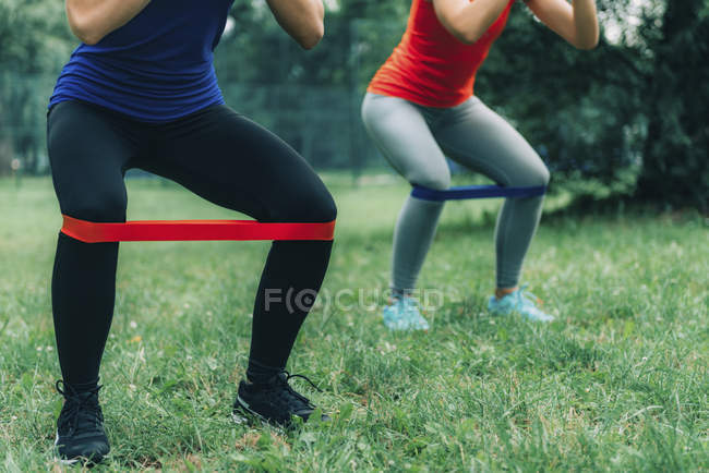 Low section of female friends exercising with elastic bands in green park. — Stock Photo