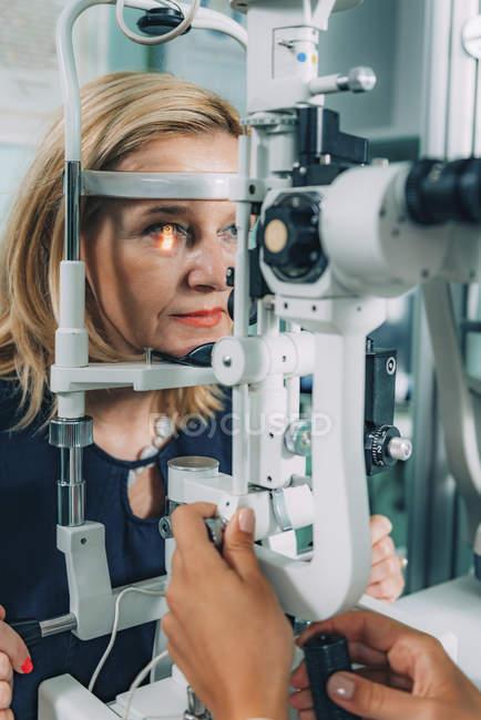 Augenarzt untersucht Patientin mit Spaltlampe in Klinik. — Stockfoto