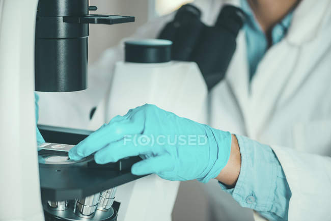 Scientist hand placing sample on slide under microscope. — Stock Photo
