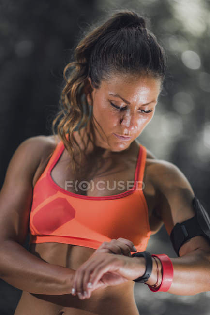 Female athlete using fitness band to track activity outdoors. — Stock Photo