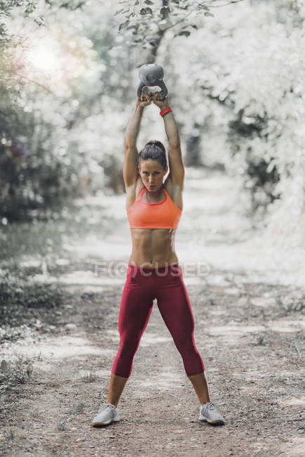 Standing female athlete exercising with kettlebell in park. — Stock Photo