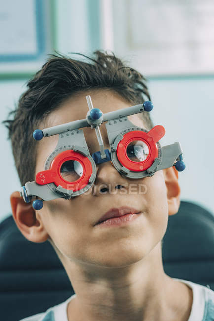 Elementary age boy in ophthalmology glasses while eye examination in clinic. — Stock Photo