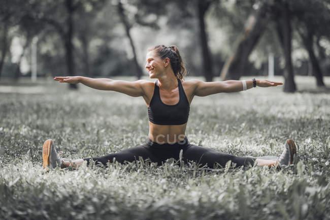 Спортивная женщина растяжения после тренировки в парке. — стоковое фото