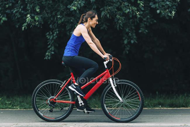 Вид сбоку улыбающейся женщины, катающейся на велосипеде в парке . — стоковое фото