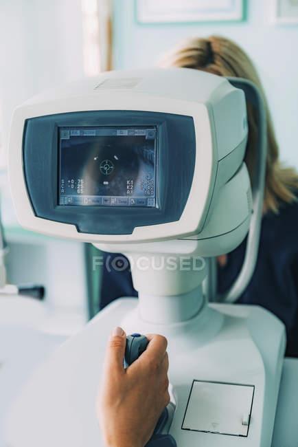 Paciente do sexo feminino submetida a exame oftalmológico com refratômetro automático . — Fotografia de Stock