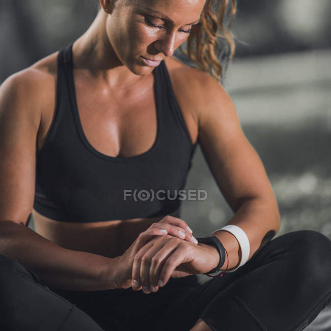 Woman checking progress on smartwatch after training outdoors. — Photo de stock