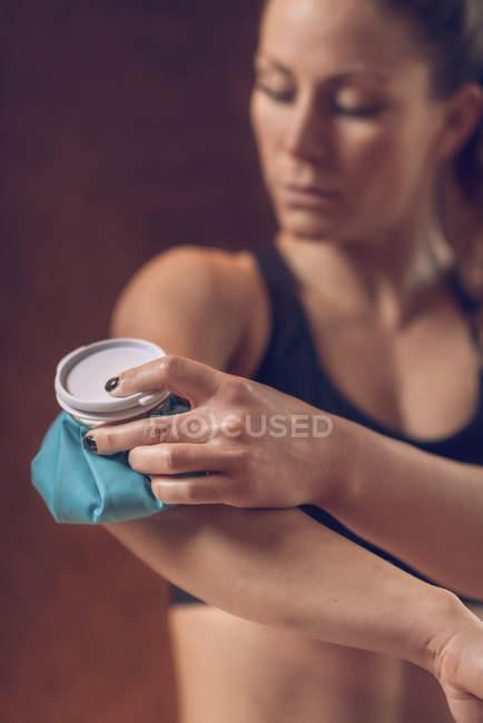 Sportswoman que prende o bloco de gelo azul no cotovelo doloroso. — Fotografia de Stock