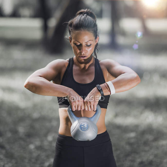 Female athlete exercising with kettlebell in park. — Stock Photo