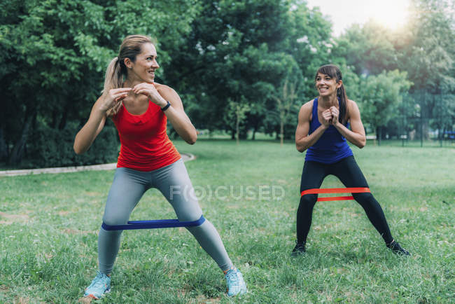 Female friends exercising with elastic bands in green park. — Stock Photo