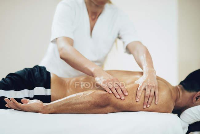 Masaje deportivo. Fisioterapeuta masajeando los brazos del hombre . - foto de stock