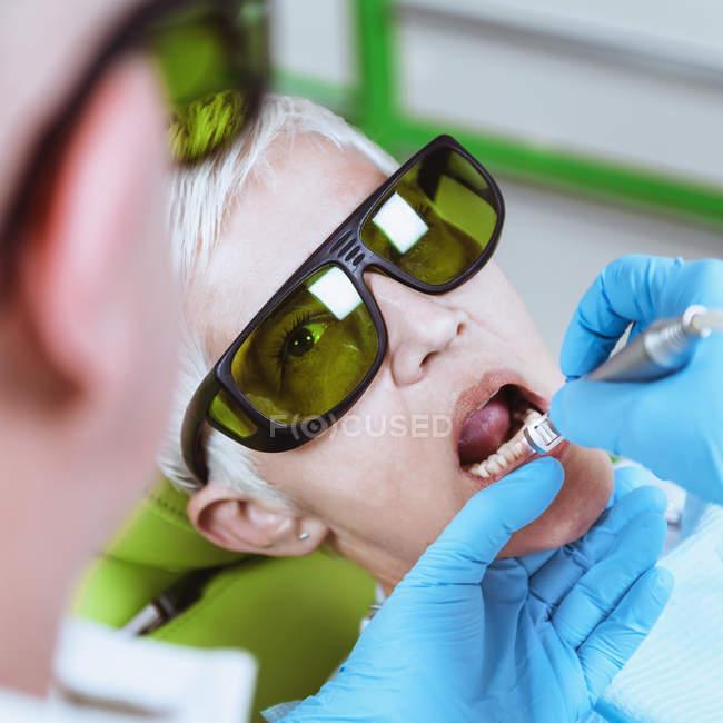 Dentista che esegue lo sbiancamento dei denti laser a paziente femminile presso la clinica dentale . — Foto stock