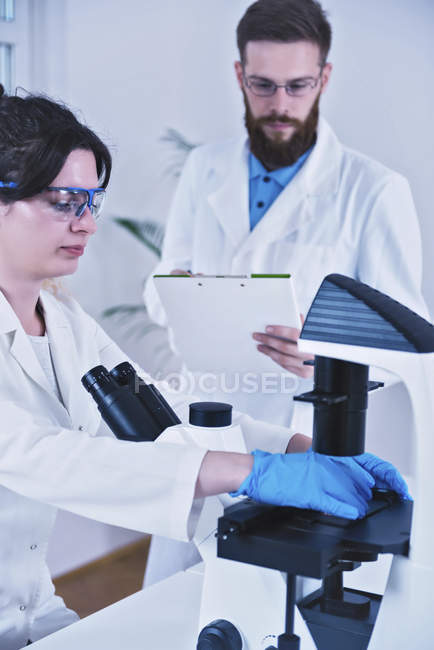 Young scientists doing test in laboratory with microscope, man taking notes. — Stock Photo