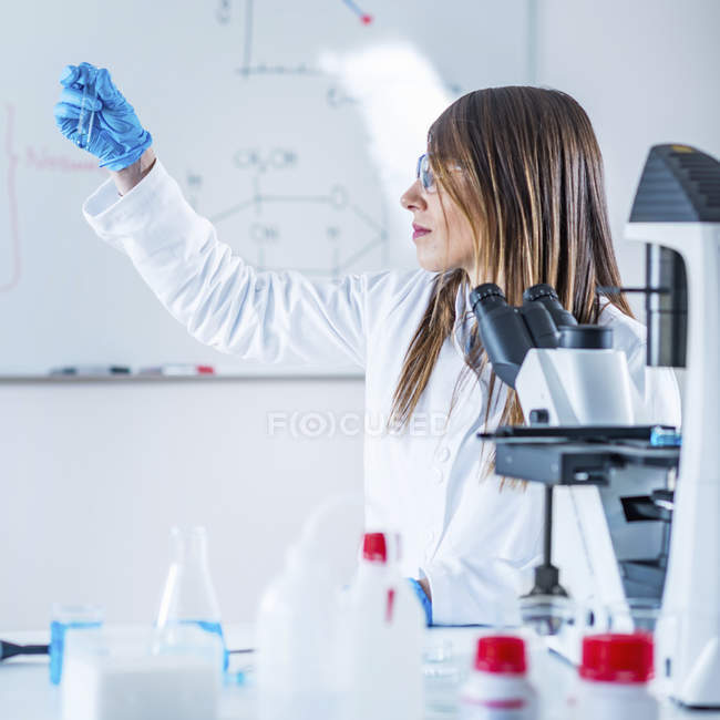 Scientific laboratory researcher using test tube and microscope. — Stock Photo