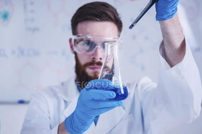 Young male scientist working in laboratory with glassware. - foto de stock