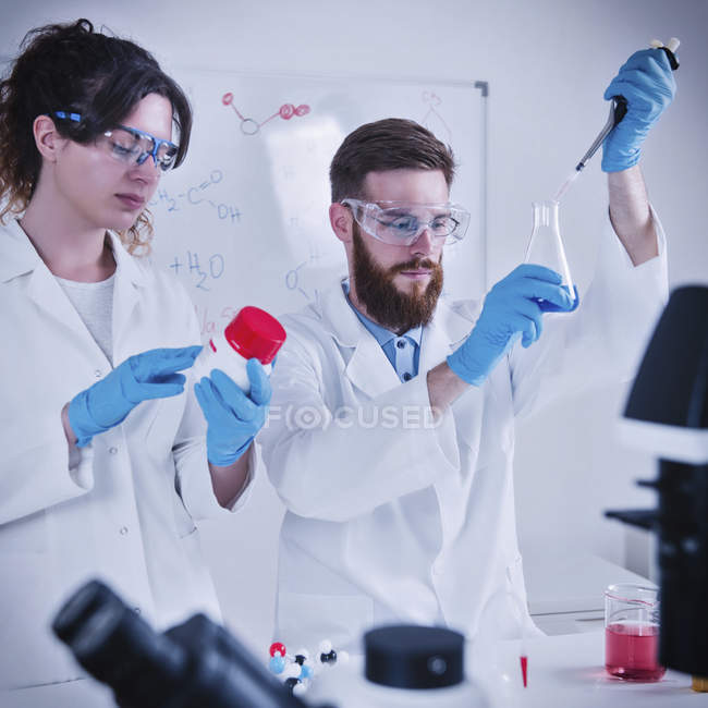 Young male and female scientists working in laboratory. — Stock Photo