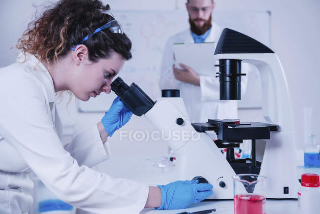 Young female scientist doing test in laboratory, male scientist standing in background in laboratory. — Stock Photo