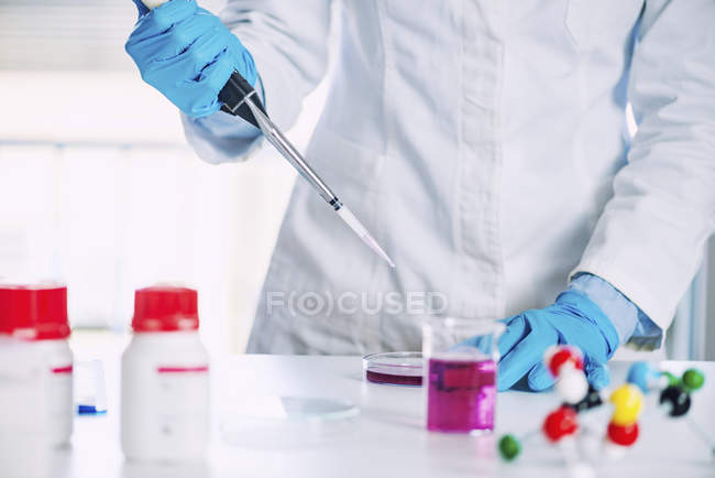 Technicien de laboratoire utilisant une micro pipette en laboratoire de chimie . — Photo de stock