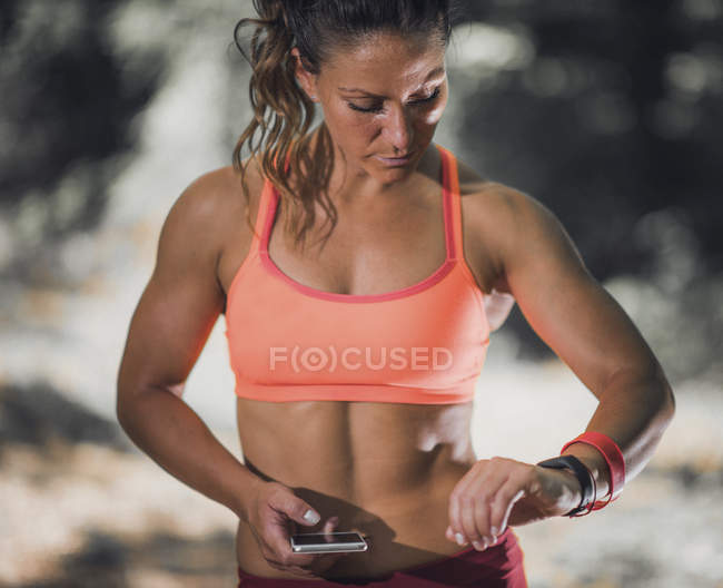Woman checking progress on smartwatch after training outdoors. — Stock Photo