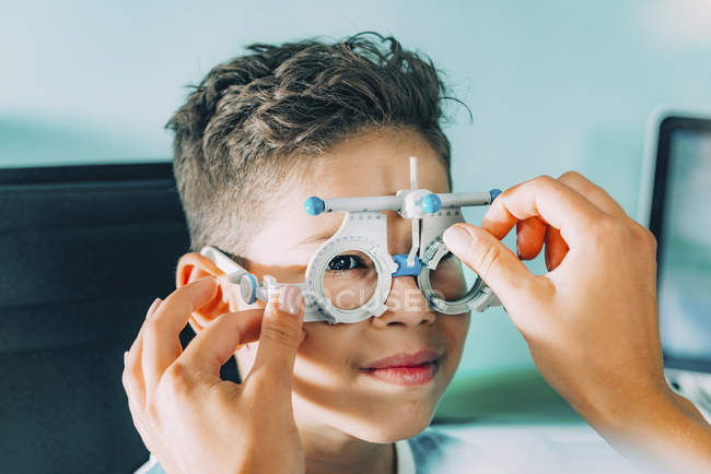 Ophthalmologist helping boy wearing glasses while eye examination in clinic. — Stock Photo