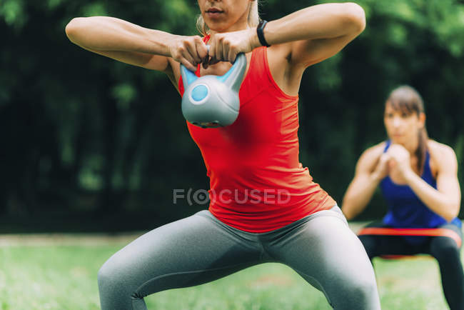Women exercising outdoors with kettlebell and elastic band. — стоковое фото