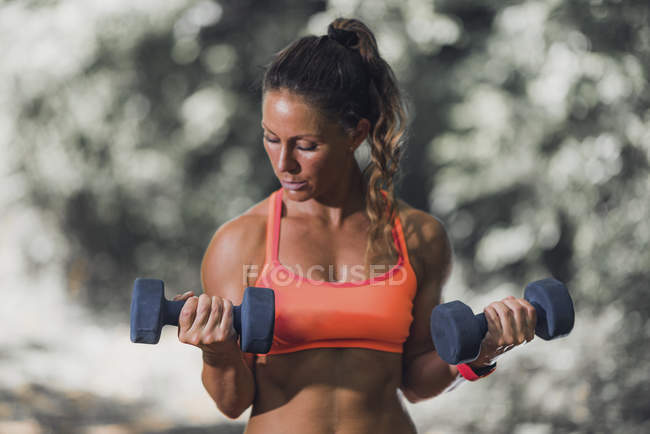 Female athlete exercising with dumbbells outdoors. — Stock Photo