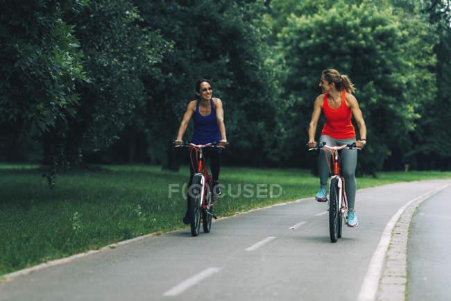 Duas mulheres andando de bicicleta juntas no parque . — Fotografia de Stock