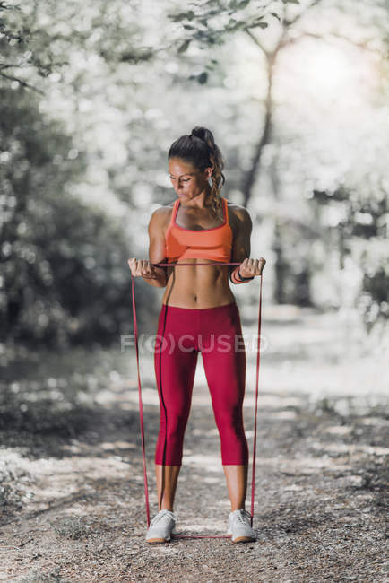 Fit woman exercising with elastic band in park. — Stock Photo