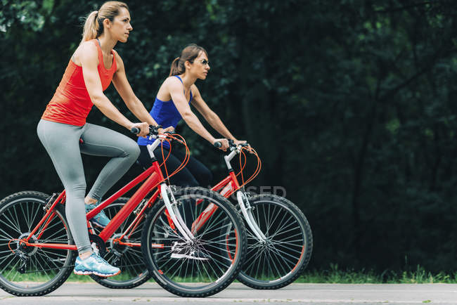 Two mid adult women cycling together in park. — Stock Photo