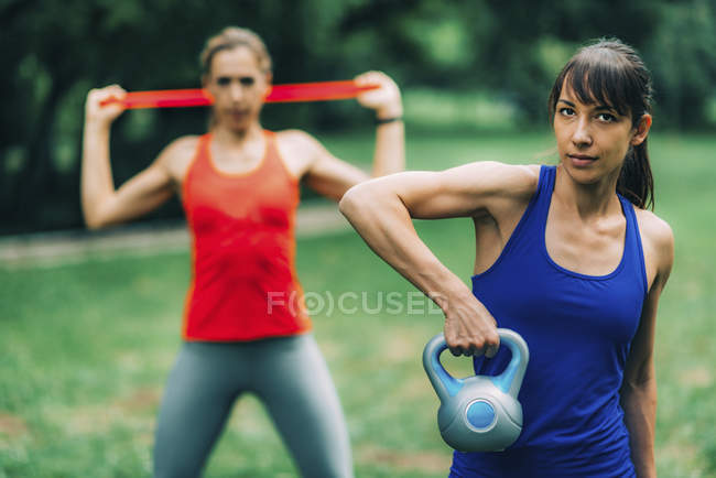 Women exercising outdoors with kettlebell and elastic band. — Stock Photo