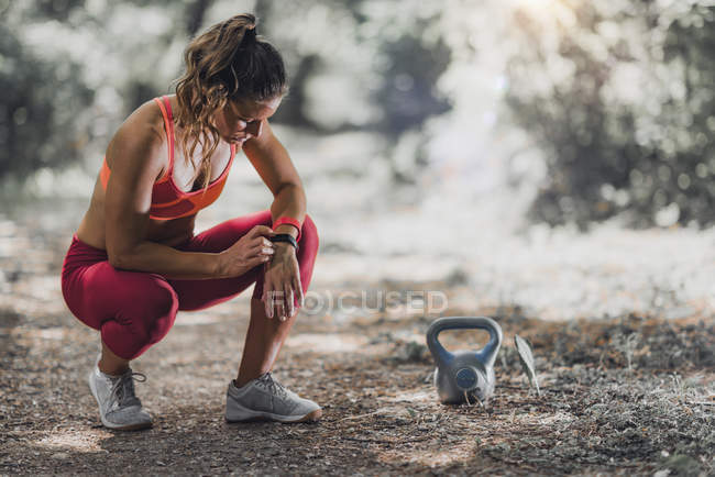 Круп'є жіночий спортсмен використання фітнес-групи для відстеження діяльності на відкритому повітрі. — стокове фото