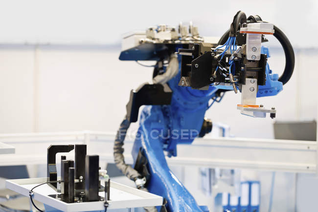 Blue industrial robotic arm in high tech factory. — Stock Photo