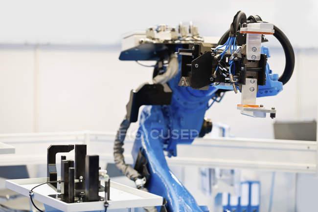 Blauer Industrieroboterarm in High-Tech-Fabrik. — Stockfoto
