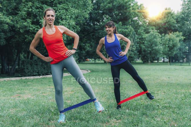 Женщины-друзья, занимающиеся спортом с эластичными лентами в зеленом парке . — стоковое фото