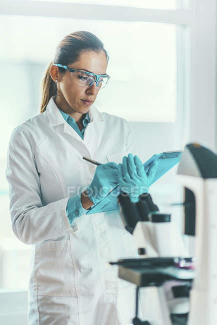 Científico de la biotecnología tomando nota mientras la investigación bioquímica . - foto de stock