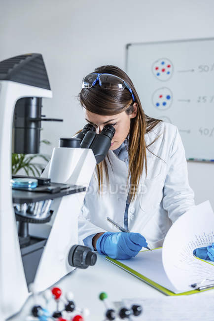 Female scientist researching sample in laboratory. — Stock Photo