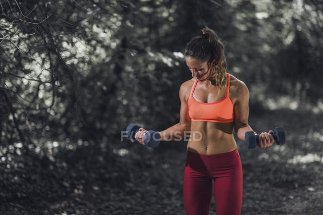 Female athlete exercising with dumbbells in park. — Stock Photo