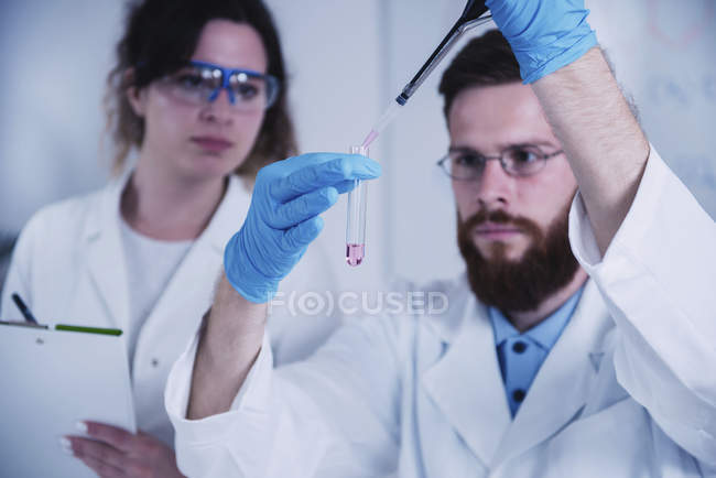 Young male and female researchers holding dropper and test tube in laboratory. — Stock Photo
